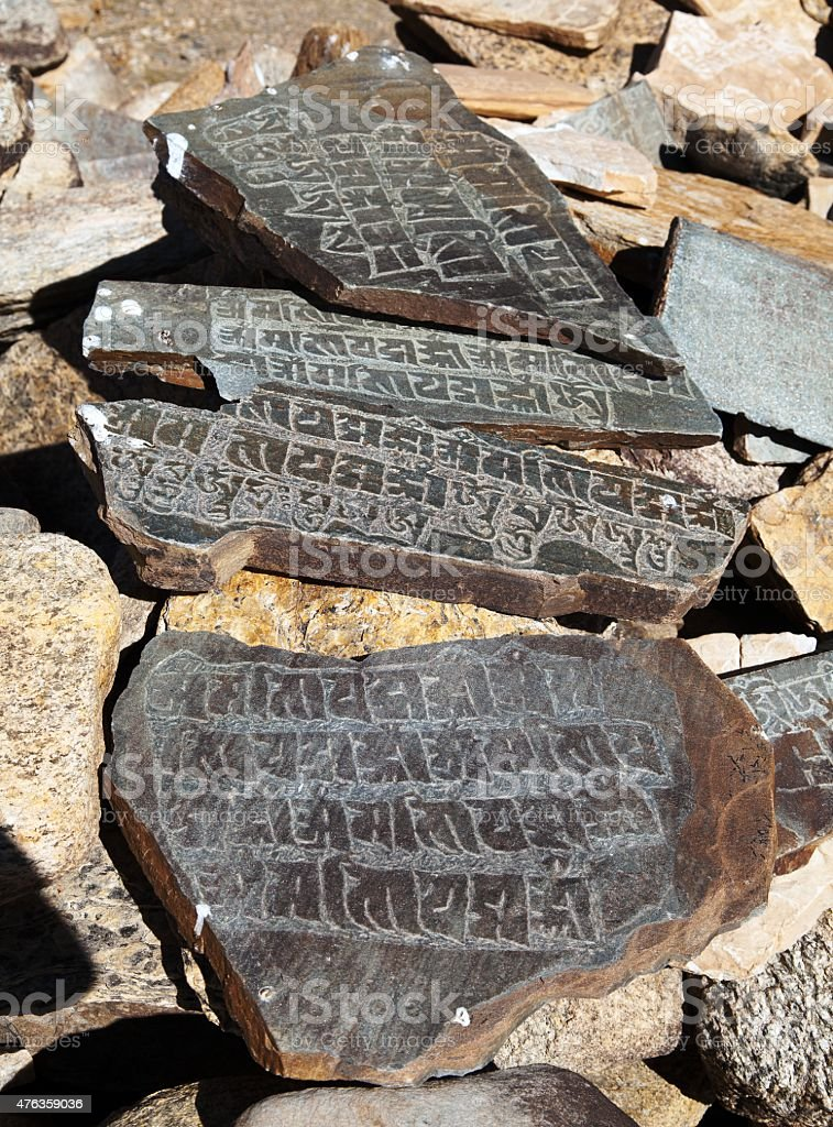 Mani wall and stone with buddhist symbols stock photo
