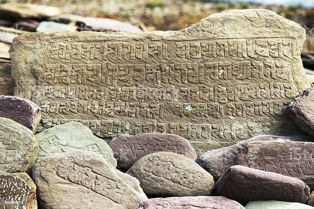 Mani wall and stones with buddhist symbols stock photo