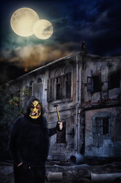 Maniac in awful mask waves a hammer stock photo