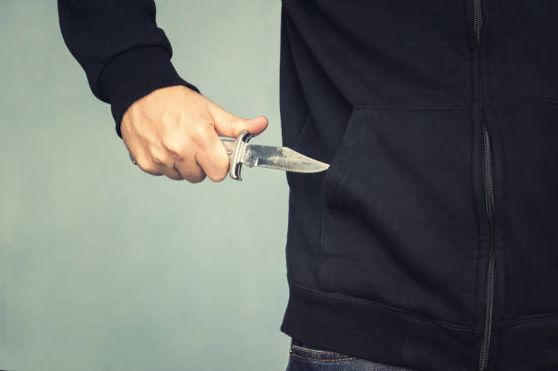 A maniac with a knife in his pocket. The murderer hides a small folding knife. Intimidation with a knife in the robbery. mafia A maniac with a knife in his pocket. The murderer hides a small folding knife. Intimidation with a knife in the robbery. mafia. cutthroat stock pictures, royalty-free photos & images