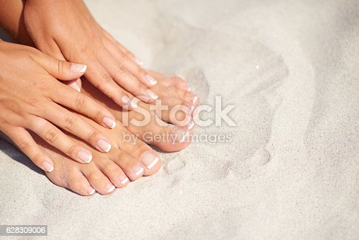 Shoot of manicure and pedicure over sand background on the beach