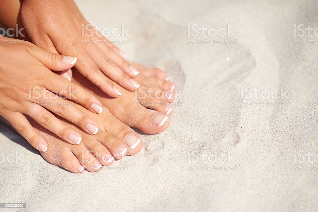 Manicure and pedicure over sand background on the beach - foto de stock