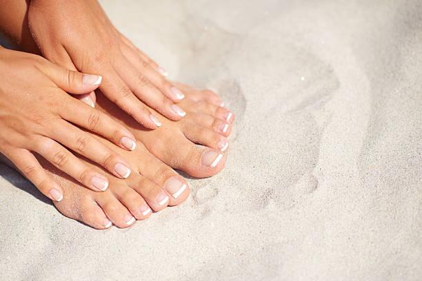 manicure and pedicure over sand background on the beach - feet hand imagens e fotografias de stock