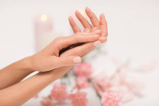 매니큐어입니다. 분홍색 꽃을 가진 백색 배경에 아름 답 고 섬세 한 손. - 매니큐어 화장품 뉴스 사진 이미지
