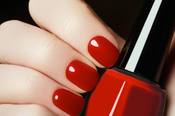 maniküre. schöne gepflegte frauenhand mit rotem nagellack - nageldesign trend stock-fotos und bilder
