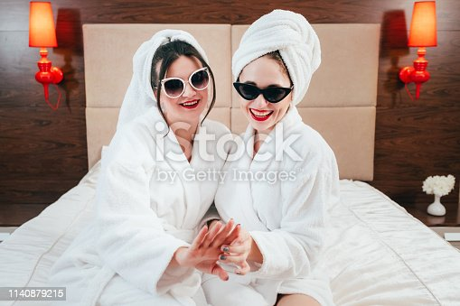 Look at my manicure. BFF beauty treatment leisure. Relaxed young women in sunglasses, bathrobes and towel turbans.