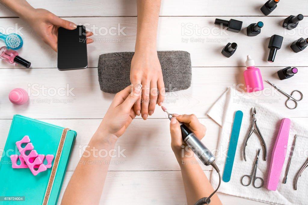 Manucure pour le client. Gros plan des mains d'un client sur un fond en bois et manucure photo libre de droits