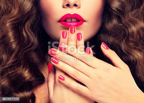 istock Manicure in a red color on the nails vivid red lipstick and dense, curly hair. 802557220