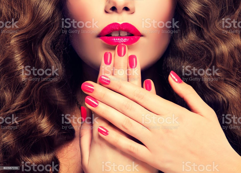Manicure in a red color on the nails vivid red lipstick and dense, curly hair. stock photo