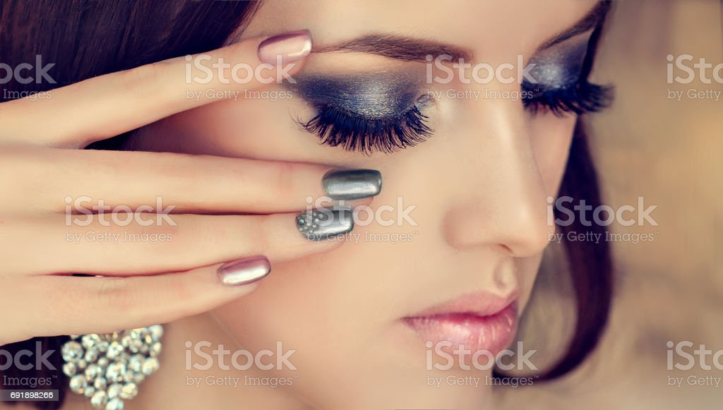 Manicure in a silver color on the nails and smokey eyes style make up. stock photo