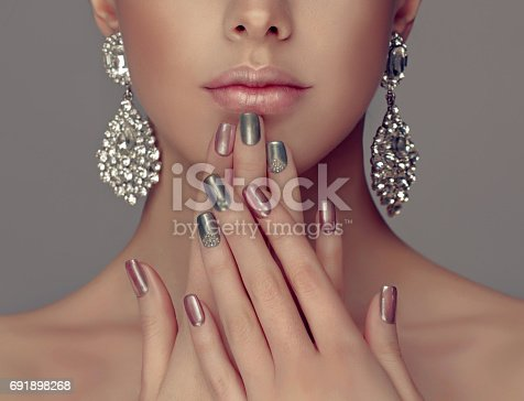 istock Manicure in a silver color on the nails and smokey eyes style make up. 691898268