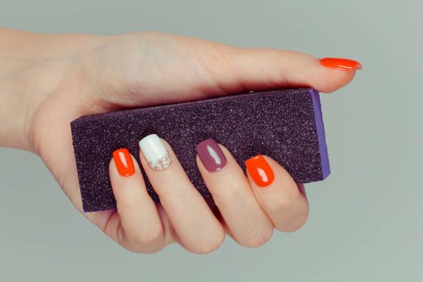 maniküre. multi farbige nagel poliert finger hand hält schwarz nagelfeile. - herbst nagellack stock-fotos und bilder
