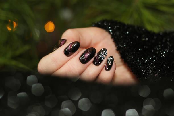 maniküre nageldesign für silvester, weihnachten katze auge effekt schwarz lila goldene chamäleon - nageldesign weihnachten stock-fotos und bilder