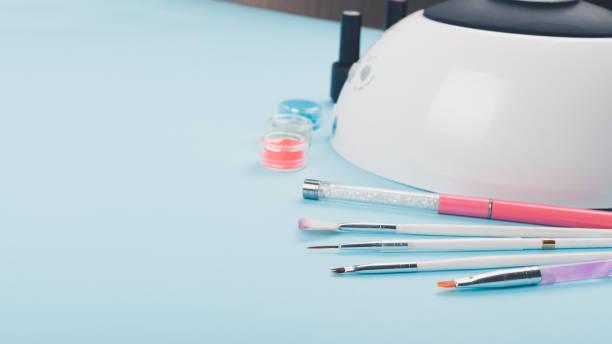 maniküre, nagel-kunst-design auf blauem hintergrund gesetzt. professionelle led tischleuchte für maniküre, gel nagellacke, farben und pigmente, dekor, bürsten und werkzeuge für nagel-design-kunst. - nägel glitzer stock-fotos und bilder
