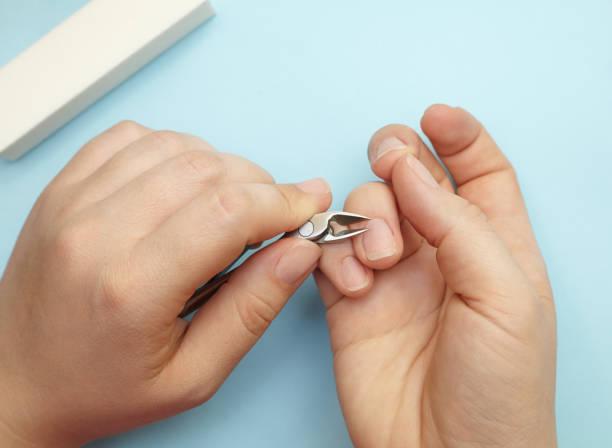 manicure van een vrouw hand, bezuinigingen nagelriemen door gesneden kniptangen, zelfzorg voor nagels - foto's van hands stockfoto's en -beelden