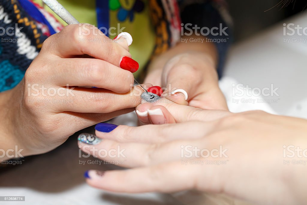 manicurist makes the new gel polish manicure, close-up, beauty and...