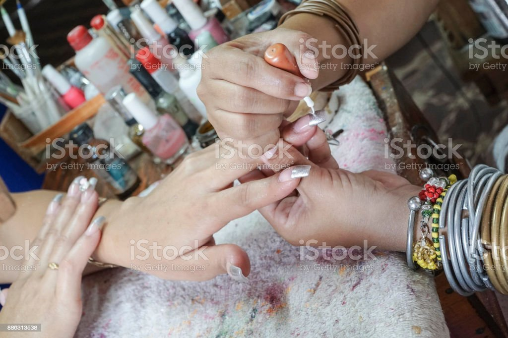 Manicure process in a beauty salon showing making of artificial nails stock photo