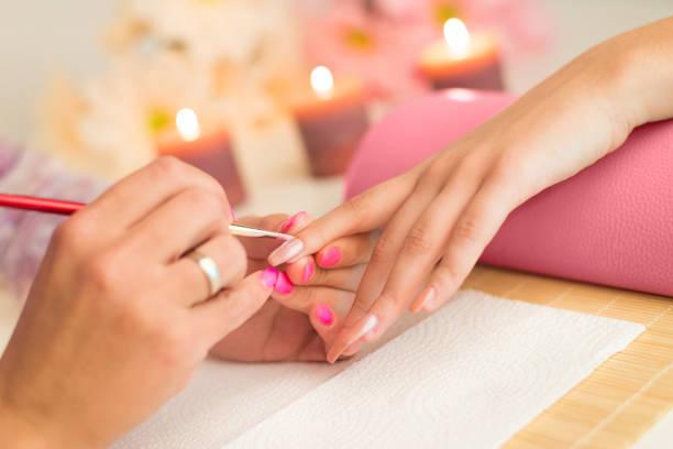 maniküre-prozess im schönheits-salon - handbemalte teller stock-fotos und bilder