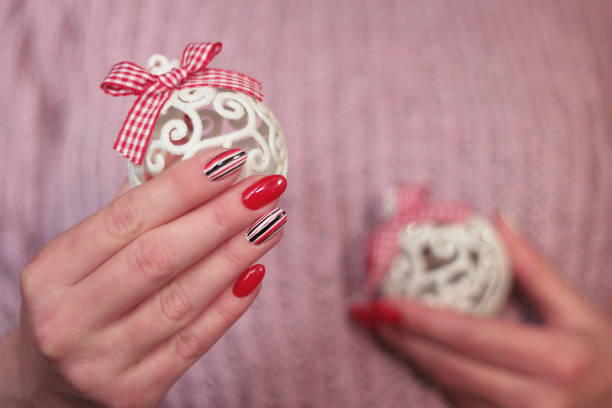 lange nägel maniküre rot mit streifen hält eine weiße weihnachtskugel - nageldesign weihnachten stock-fotos und bilder