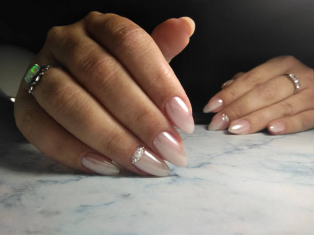 manicure with shiny coating and lined with rhinestones. pearl design with pink tint. - cuticle stock pictures, royalty-free photos & images