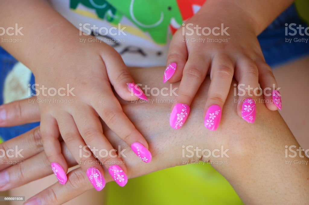 Manicured girl's hand on mother's hand stock photo