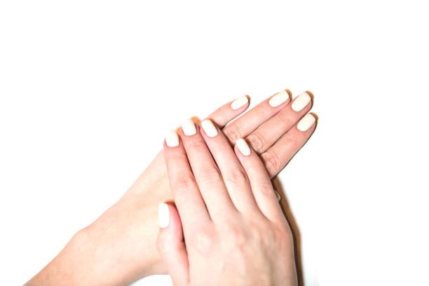 gepflegte hände isoliert auf weißem hintergrund. hände mit gepflegten nägeln gefärbt mit weißer nagellack. - gelnägel stock-fotos und bilder