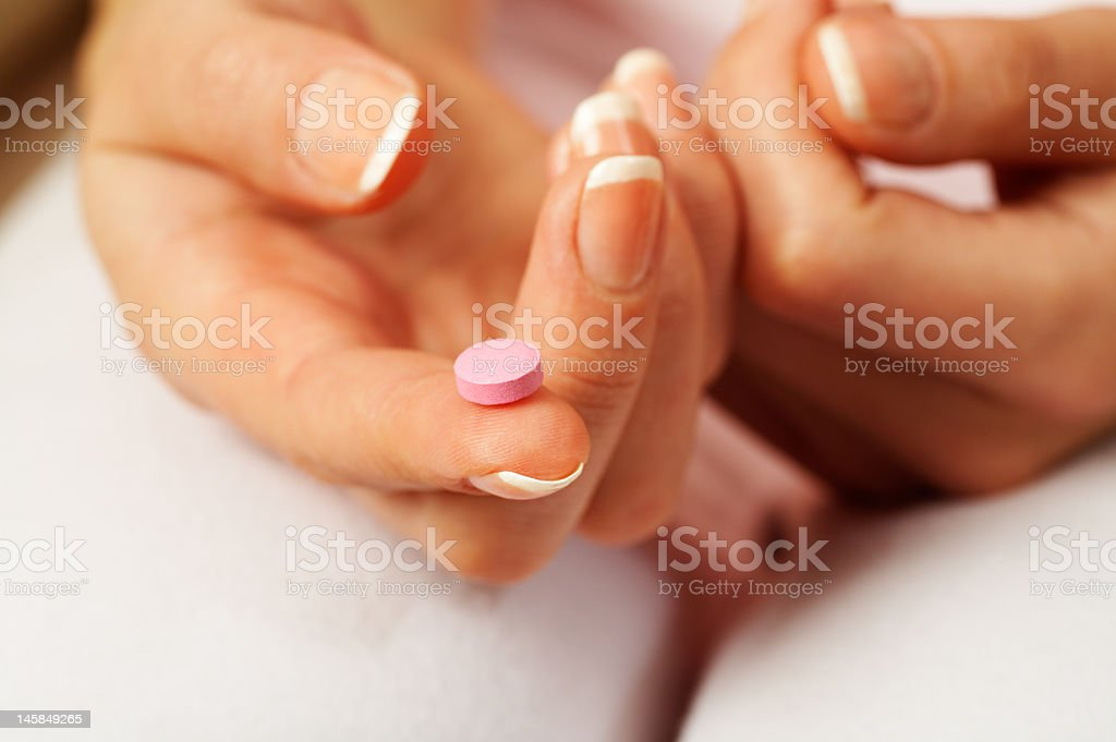 Manicured hands showing mauve tablet on finger  royalty-free stock photo