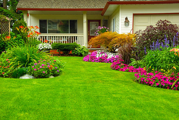 Manicured House and Garden Manicured House and Garden displaying annual and perennial gardens in full bloom. lawn stock pictures, royalty-free photos & images