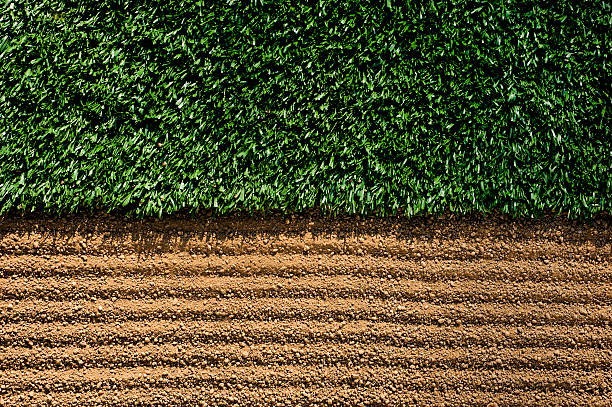 Manicured Sports Field between turf and dirt Manicured Sports Field. Freshly manicured dirt with rake grooves next to artificial turf as the sun casts shadows. infield stock pictures, royalty-free photos & images
