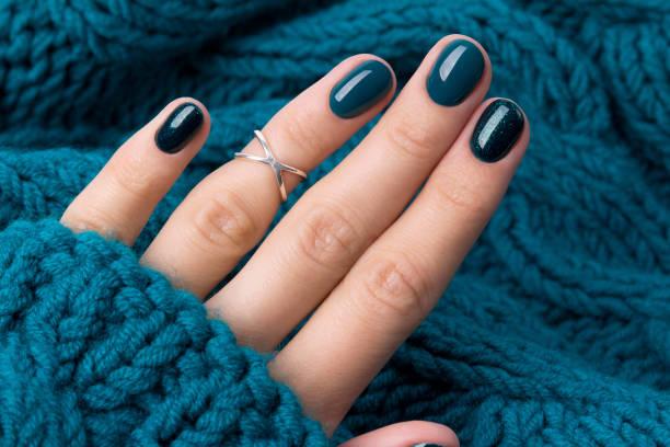 manikürte frau hand in warmen wolle türkis pullover - herbst nagellack stock-fotos und bilder