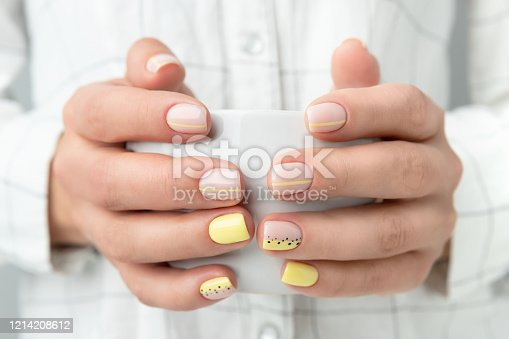 Manicured woman's hands holding a cup of coffee or tea. Spring summer yellow manicure design close up
