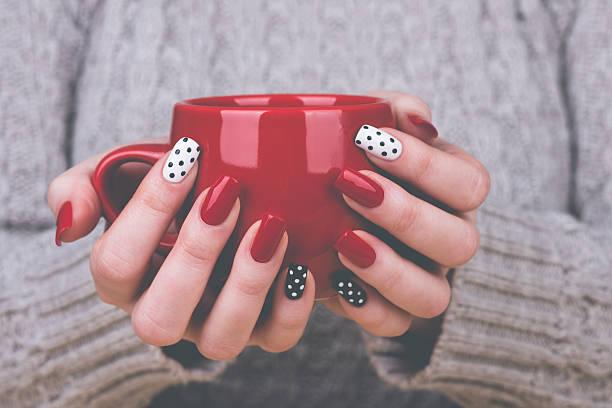 gepflegte frau hände holding cup - nailstudio stock-fotos und bilder