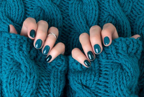 manikürte frau hände in warmen wolle türkis pullover - herbst nagellack stock-fotos und bilder