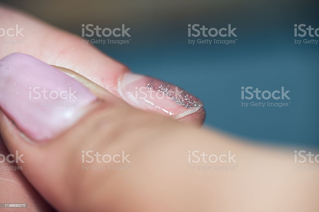 A close-up shot of a manicurist applying silver glitter on gel nail...