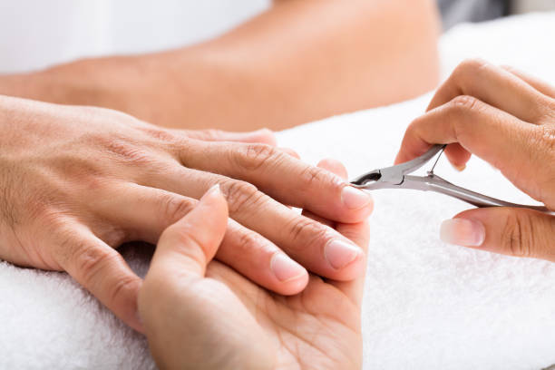 manicurist cutting off the cuticle from the person's fingers - cuticle stock pictures, royalty-free photos & images