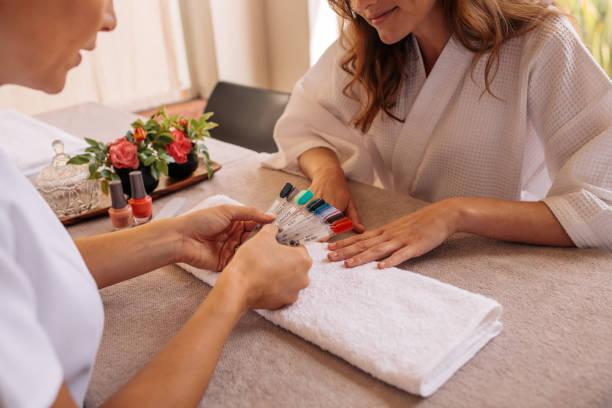 maniküre mit proben von nagel muster an client - nailstudio stock-fotos und bilder