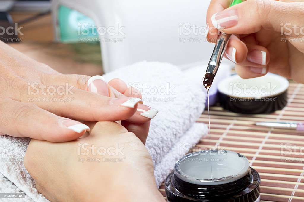 Manicurist doing white French manicure stock photo
