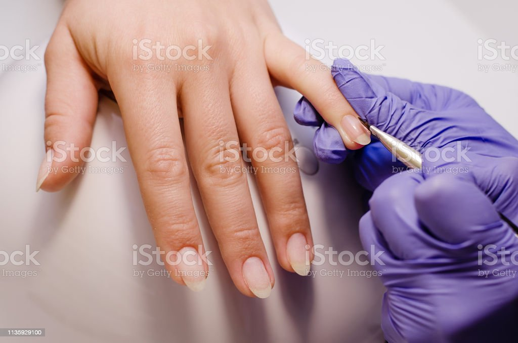 Closeup shot of master in rubber gloves covering nails with base gel...