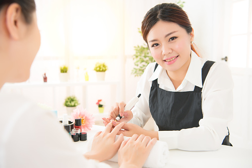 istock Manicurist is applying electric nail file drill 823559752