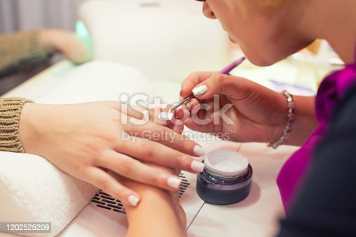 Young woman getting artificial nails in the professional nail salon.