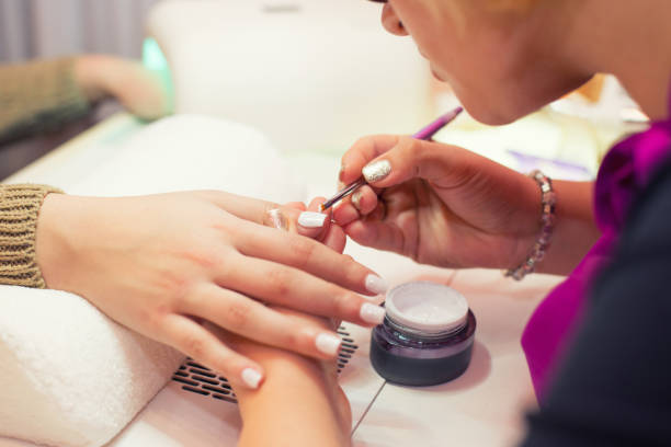 Manicurist making artificial nails in the nail salon stock photo