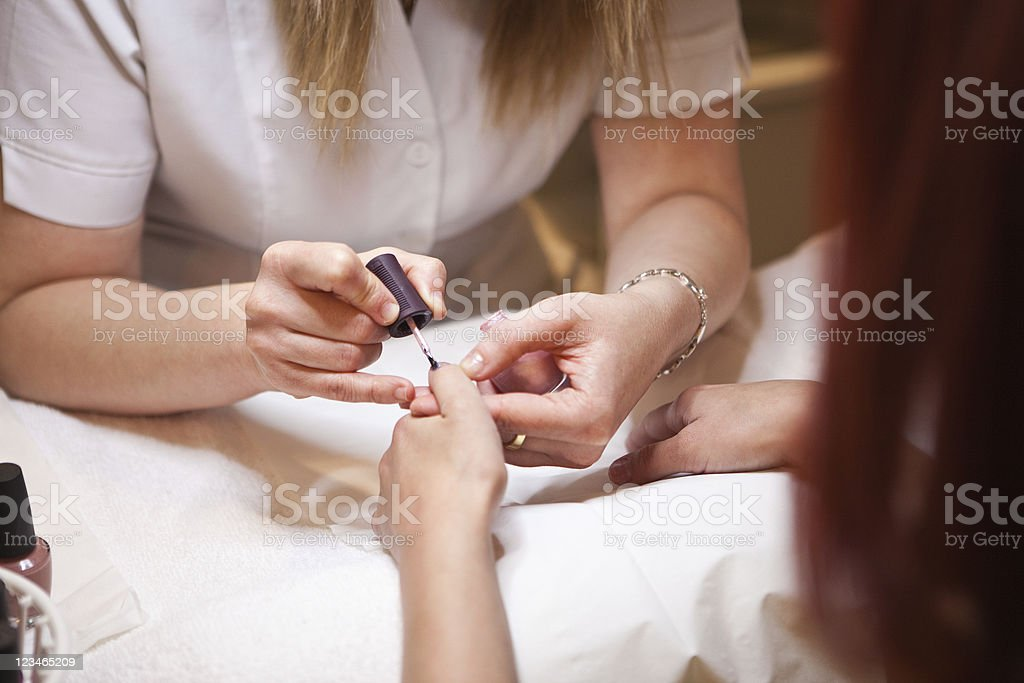 Manicurist painting customer`s nails royalty-free stock photo
