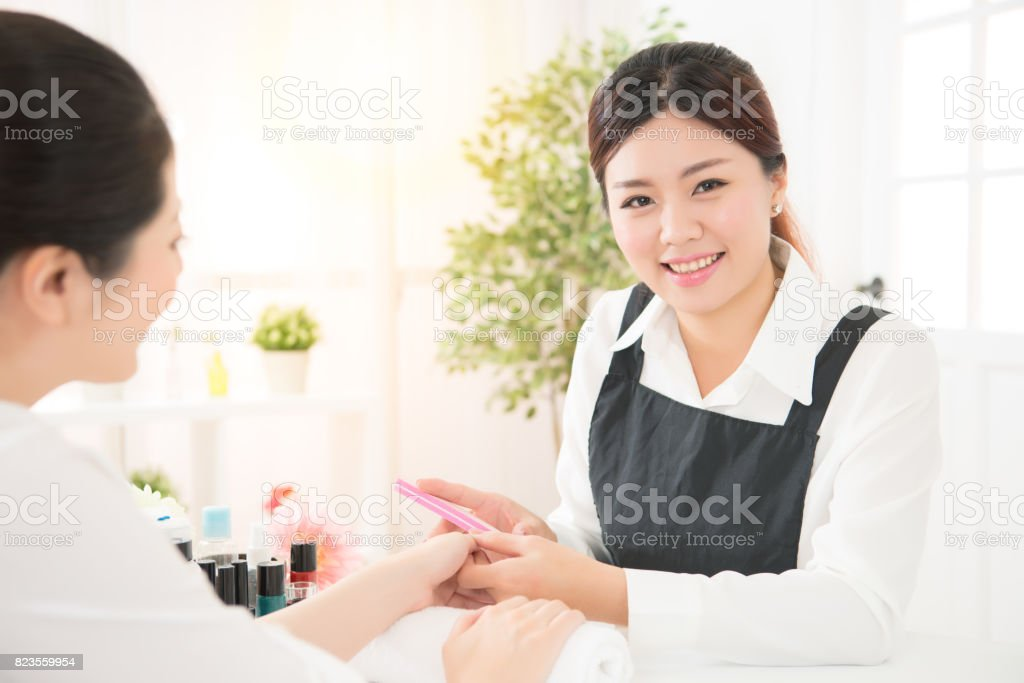 manicurist take care nails by using polisher stock photo