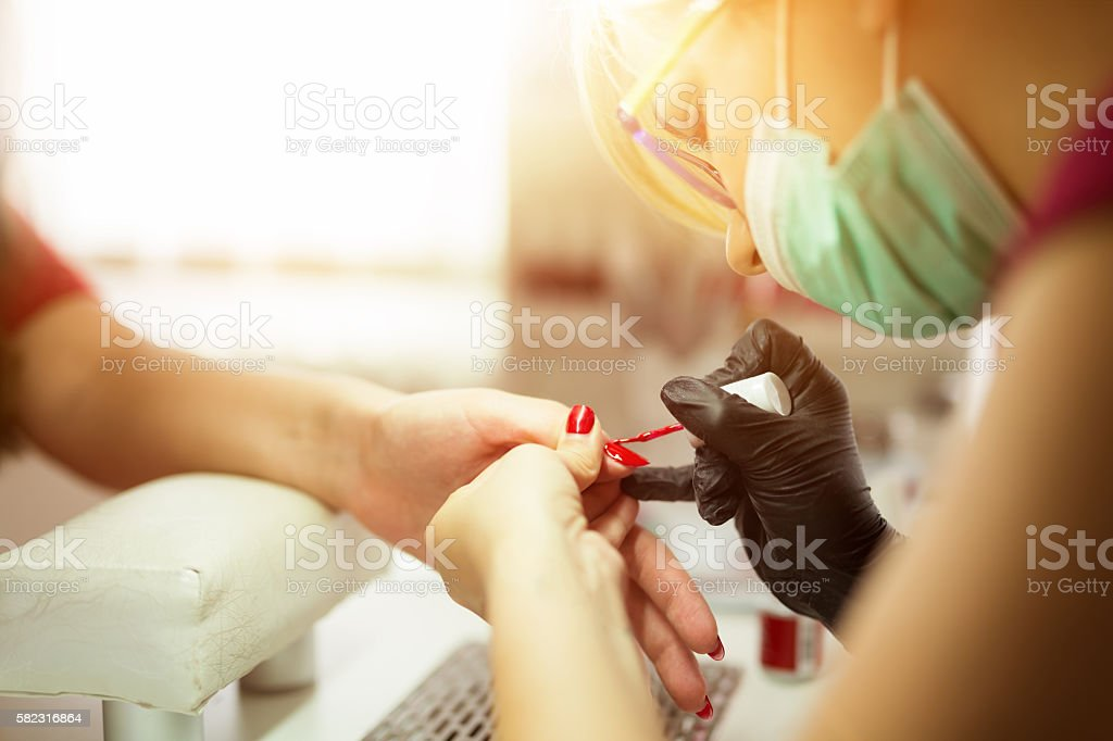 Manicurist working on client nails stock photo