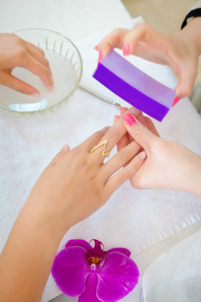 Manicurists and Pedicurists Serving Customers in Nail Spa Salon Manicure and pedicure salon serving Customer in a spa salon. An Asian owned small business in personal body care. A manicure in progress. pedicure manicure men beauty spa stock pictures, royalty-free photos & images