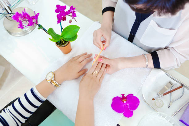 Manicurists and Pedicurists Serving Customers in Nail Spa Salon stock photo