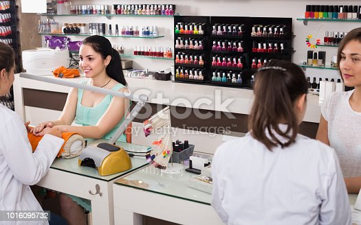 istock Manicurists giving manicure to female clients at nail salon 1016095732