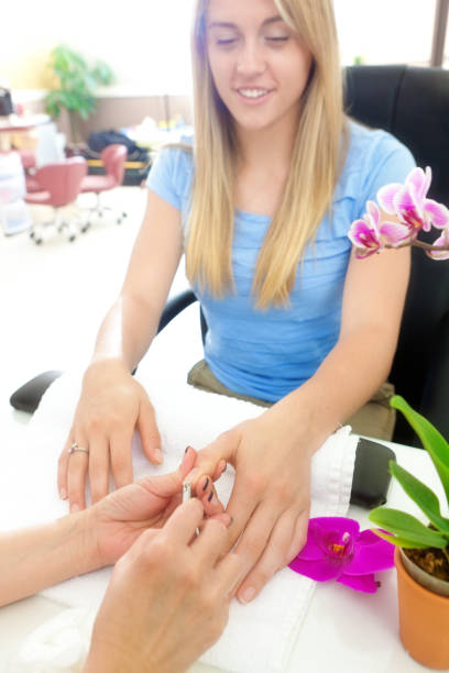 Manicurists Serving Customers in Nail Spa Salon Manicurist serving woman customer in a spa salon. An Asian owned small business in personal body care. A manicure in progress. pedicure manicure men beauty spa stock pictures, royalty-free photos & images