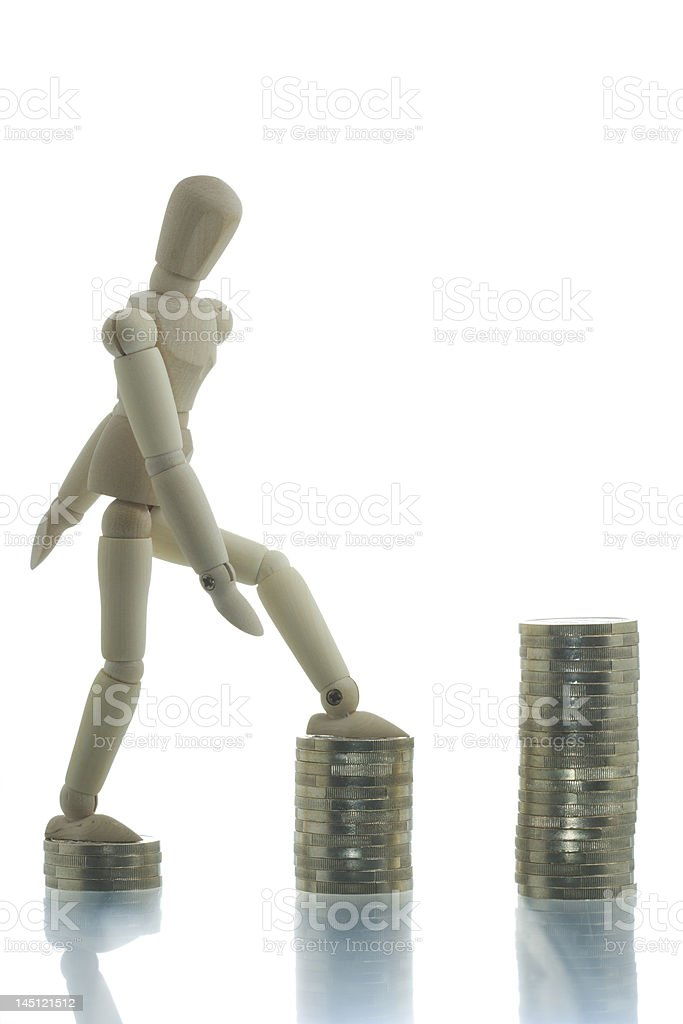 Manikin going up the coin piles royalty-free stock photo