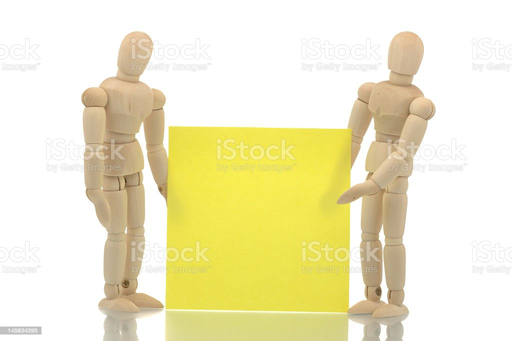 Manikins holding and pointing to a note royalty-free stock photo